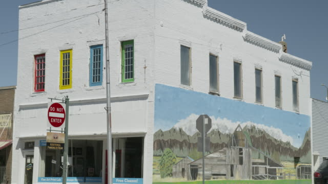 vidéos et rushes de medium tilt up shot to building with mural in small town / payson, utah, united states - payson