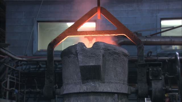 medium tilt-down - steam rises from a vat of molten metal as it moves in a foundry /  ohio, united states - vat stock videos & royalty-free footage