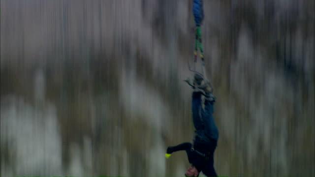 vídeos y material grabado en eventos de stock de medium tilt-down tilt-up - a bungee jumper leaps from a high bridge / italy - puenting