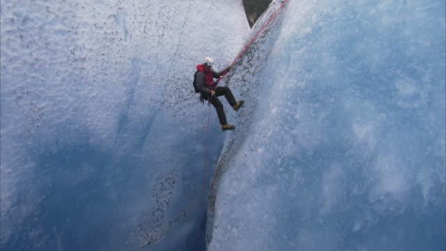 """Medium tilt-down-Ice climbers rappel into a crevasse in the Juneau Ice Fields. / Alaska, USA"""