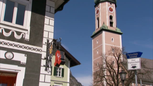 vídeos de stock, filmes e b-roll de medium tilt-up - a bell tower rises above a street in garmisch-partenkirchen, germany. / garmisch-partenkirchen, germany - garmisch partenkirchen
