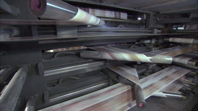 vídeos de stock, filmes e b-roll de medium tilt-up - long sheets of printed paper roll through a printing press /  wisconsin, united states - revista publicação