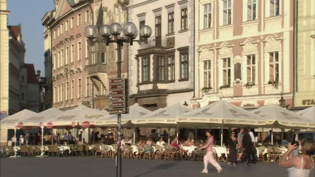 Medium tilt-up-Pedestrians pass through a marketplace in Prague. / Prague, Czech Republic