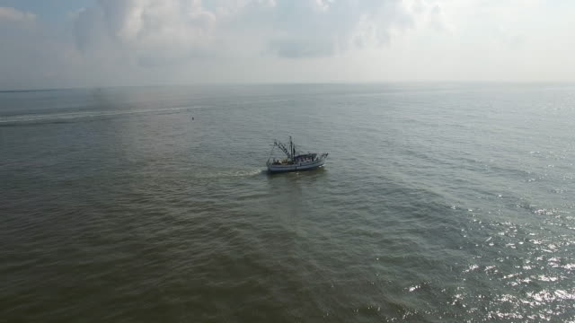 vidéos et rushes de medium to close fly to shrimp fishing boat - drone aerial view 4k prawn fishing, shrimp boat, trawler, trawling for ocean fish in the open sea, heavy waves and nets in the water on louisiana, mississippi coast, gulf coast 4k transportation - industrie de la pêche