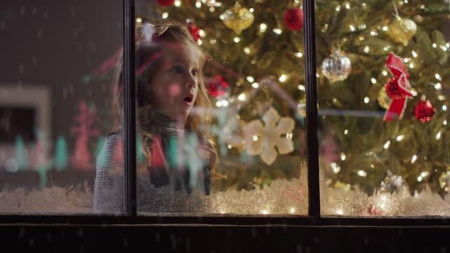 medium to close up shot of surprised girl looking out window on christmas / cedar hills, utah, united states - 驚き点の映像素材/bロール