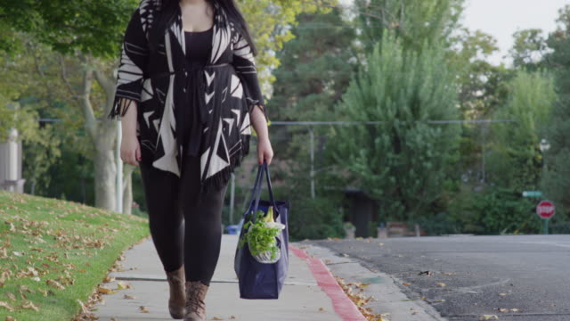 medium to close up shot of woman carrying groceries on sidewalk / orem, utah, united states - overweight stock-videos und b-roll-filmmaterial