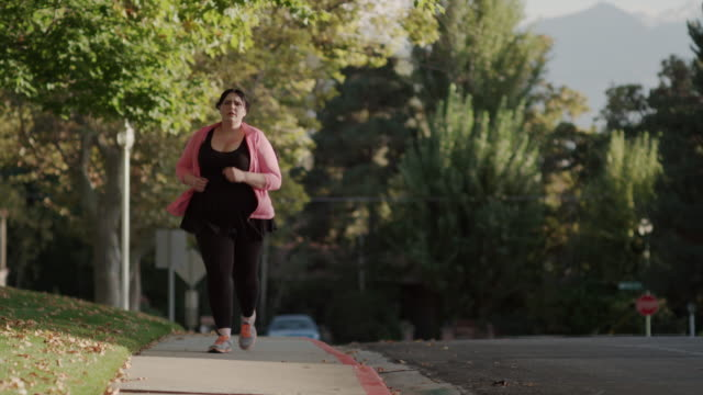 medium to close up shot of woman fatigued after jogging on sidewalk / orem, utah, united states - overweight stock-videos und b-roll-filmmaterial