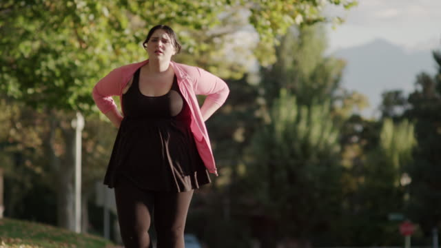 medium to close up slow motion shot of jogging woman fatigued on sidewalk / orem, utah, united states - overweight stock-videos und b-roll-filmmaterial
