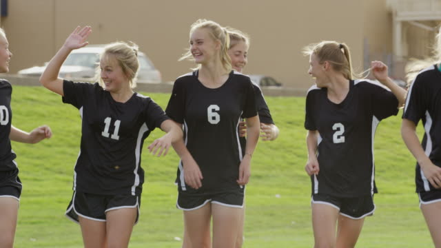 Medium to close up slow motion shot of soccer players celebrating / Springville, Utah, United States