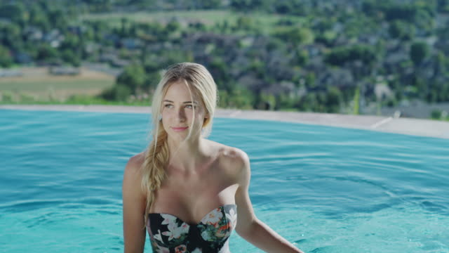 medium to close up slow motion shot of woman exiting swimming pool / cedar hills, utah, united states - 美しい女性点の映像素材/bロール