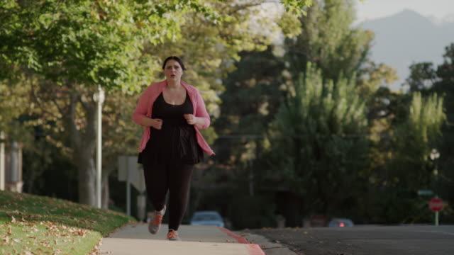 Medium to close up slow motion shot of woman jogging on sidewalk / Orem, Utah, United States