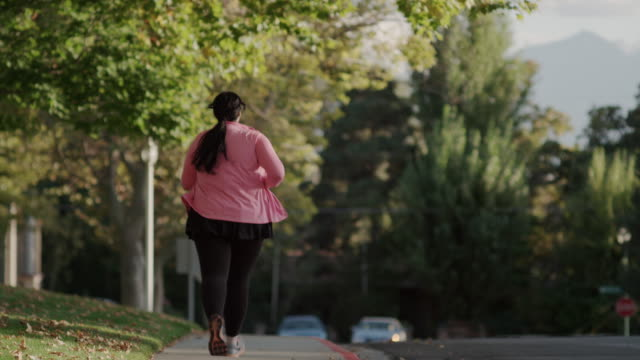 medium to wide slow motion shot of woman jogging on sidewalk / orem, utah, united states - overweight active stock videos & royalty-free footage