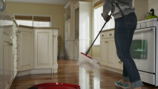 """Medium tracking panning shot of woman mopping kitchen floor / Cedar Hills, Utah, United States"""