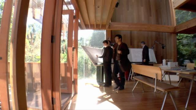 medium tracking shot architect leaving office and walking through office corridor - 製図板点の映像素材/bロール