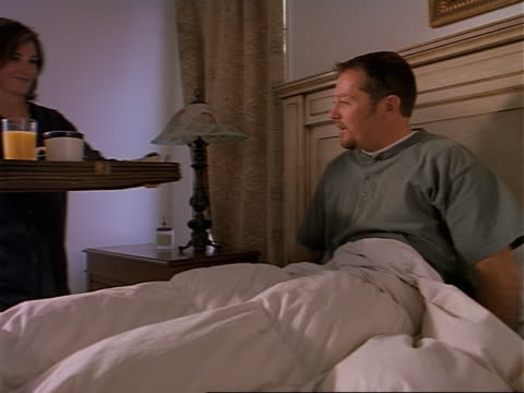 medium tracking shot as a caucasian woman brings her husband breakfast in bed