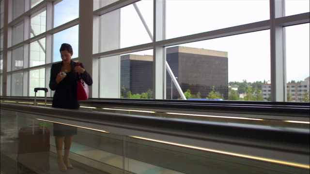 stockvideo's en b-roll-footage met medium tracking shot businesswoman on moving sidewalk in airport/ seattle - voetgangerspad