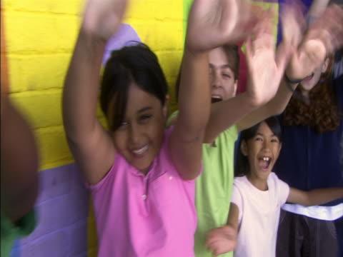 medium tracking shot children standing up against wall, waving arms and smiling/ back down line of children/ london, england - menschliche gliedmaßen stock-videos und b-roll-filmmaterial