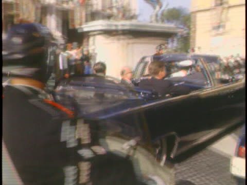 medium tracking shot follows a convertible carrying president john f kennedy as he passes by in a presidential motorcade kennedy slightly waves to a... - united states and (politics or government) stock videos & royalty-free footage