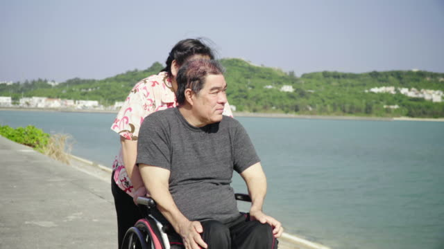 medium tracking shot of a senior woman taking her husband, who is in a wheelchair, for a walk in a park - 介護点の映像素材/bロール