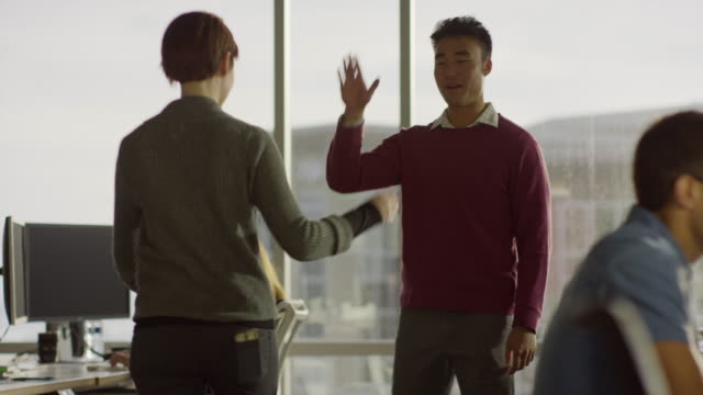 vídeos de stock, filmes e b-roll de medium tracking shot of business people high-fiving in office / lehi, utah, united states - high five