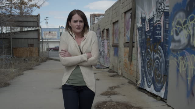 vidéos et rushes de medium tracking shot of concerned woman walking in urban alley / salt lake city, utah, united states - fragilité