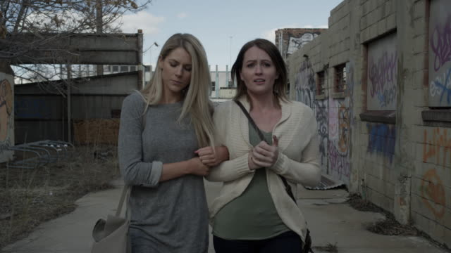 medium tracking shot of concerned women walking in urban alley / salt lake city, utah, united states - fragility stock videos & royalty-free footage
