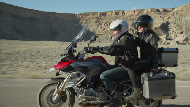 Medium tracking shot of couple riding motorcycle on desert road / Ferron, Utah, United States