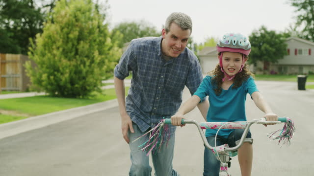 Medium tracking shot of father teaching daughter to ride bicycle / Provo, Utah, United States