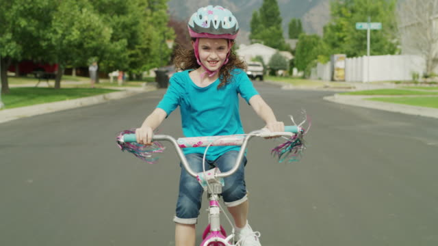 medium tracking shot of girl riding bicycle in street / provo, utah, united states - helmet stock videos & royalty-free footage
