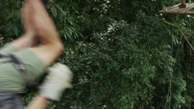 medium tracking shot of man swinging on zipline in rain forest / quepos, puntarenas, costa rica - zip line stock videos & royalty-free footage