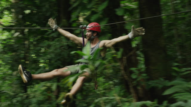 Medium tracking shot of man ziplining in rain forest / Quepos, Puntarenas, Costa Rica