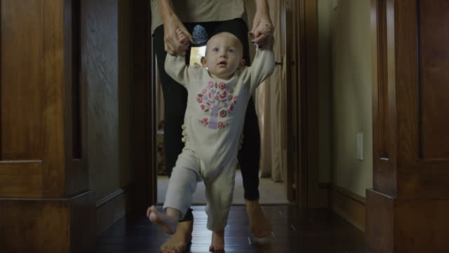 medium tracking shot of mother helping baby daughter walk / cedar hills, utah, united states - nederdel bildbanksvideor och videomaterial från bakom kulisserna