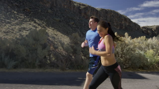 vídeos de stock, filmes e b-roll de medium tracking shot of playful couple running in neighborhood / antimony, utah, united states - sutiã para esportes