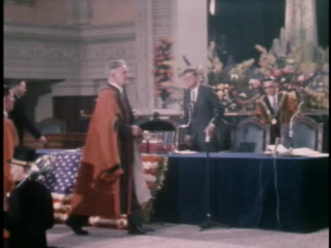medium tracking shot of president john f. kennedy as he walks onto a stage alongside a minister in what looks to be a church of some kind. the two... - (war or terrorism or election or government or illness or news event or speech or politics or politician or conflict or military or extreme weather or business or economy) and not usa stock videos & royalty-free footage