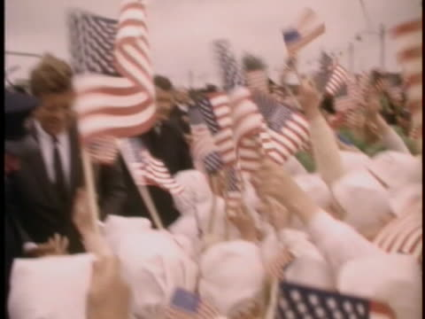 medium tracking shot of president john f. kennedy as he walks past the cameraman and towards a large crowd of children waving small american flags.... - group of people stock videos & royalty-free footage