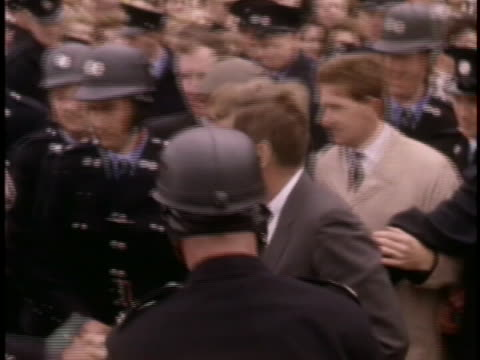 medium tracking shot of president john f. kennedy as he walks through a group of police officers. he is wearing a dark grey suit and a dark tie, and... - crime or recreational drug or prison or legal trial stock videos & royalty-free footage