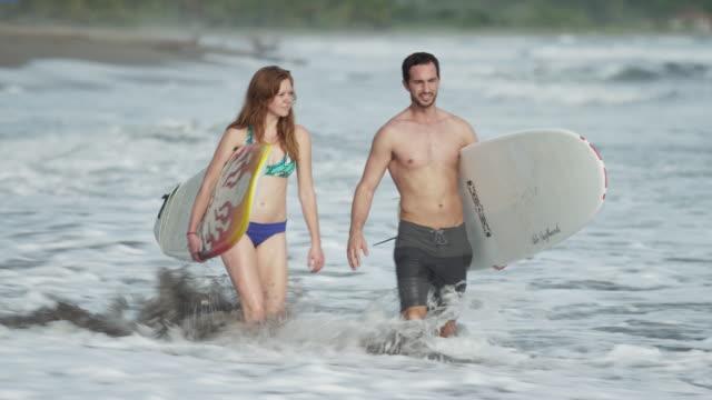 Medium tracking shot of surfers carrying surfboards in waves / Esterillos, Puntarenas, Costa Rica