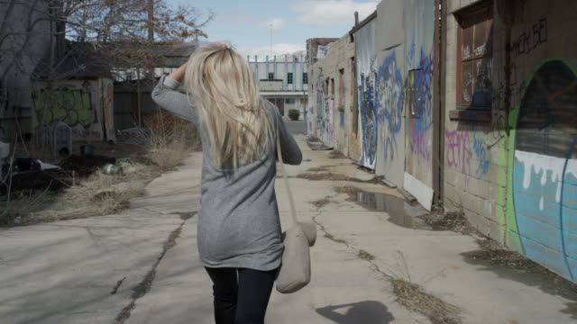 Medium tracking shot of woman running away in alley / Salt Lake City, Utah, United States