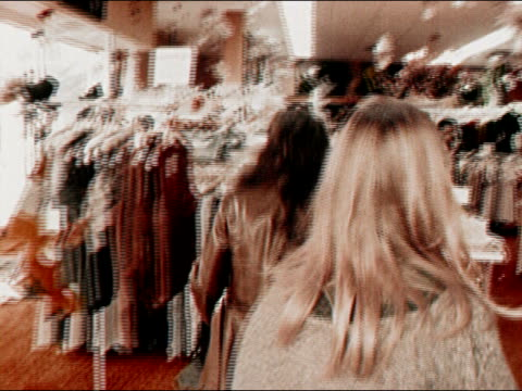 1971 medium tracking shot two young women wallking into clothing store/ california/ audio - clothing store stock videos & royalty-free footage