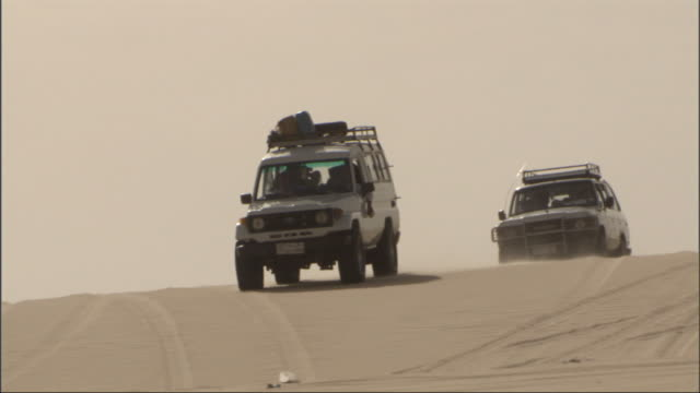 Medium, tracking-left - Two vehicles drive down a sand dune in the Sahara Desert in Egypt