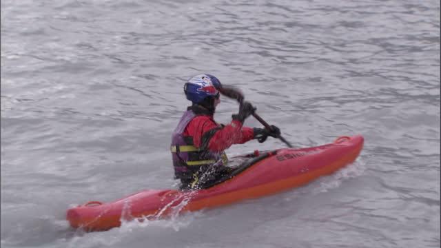 medium tracking-right - a kayaker slides off a glacier and into icy waters where he paddles away / alaska, usa - polarklimat bildbanksvideor och videomaterial från bakom kulisserna