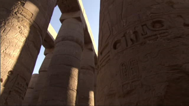 Medium, tracking-right - Carvings of hieroglyphs are seen on the ruins of old Egyptian adobe buildings