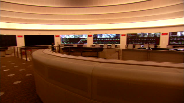 medium tracking-right - wall monitors surround the interior of the metro control center./beijing, china - control room stock videos and b-roll footage