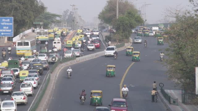 stockvideo's en b-roll-footage met ws medium traffic on big city road / delhi, delhi , india - straatnaambord