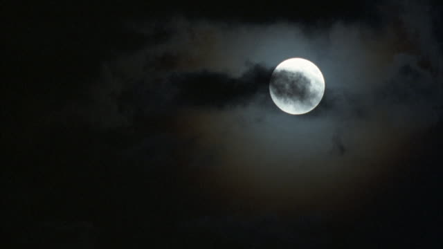 medium view of dark wispy clouds passing in front of a bright, full moon. - emergere video stock e b–roll