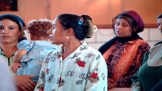 stockvideo's en b-roll-footage met medium view of female coptic worshippers chatting during a church service - gelovige