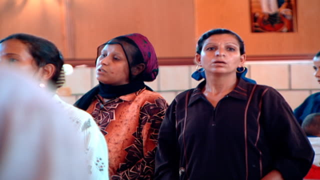 stockvideo's en b-roll-footage met medium view of female coptic worshippers wearing headscarves in a church - gelovige