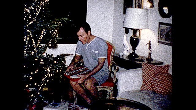 medium view of man presenting his christmas clothes with a wig on, rests on couch; full view of man sitting next to christmas tree, grabs present;... - pyjamas stock videos & royalty-free footage
