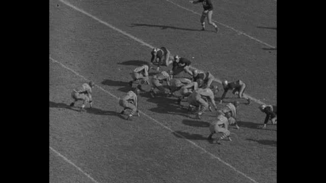 Medium wide shot Columbia University Lions and Army West Point Black Knights football teams facing each other in formation Army on offense gets ball...