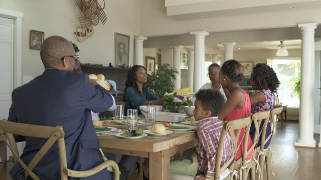 medium wide shot of a family meal - esstisch stock-videos und b-roll-filmmaterial